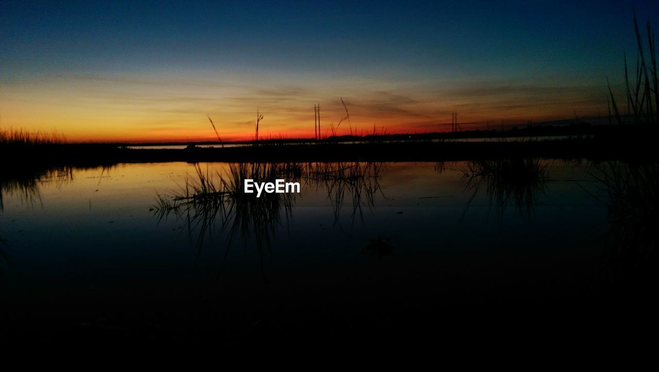 reflection, sunset, silhouette, lake, tranquility, nature, tranquil scene, water, scenics, no people, beauty in nature, sky, outdoors, standing water, dusk, day