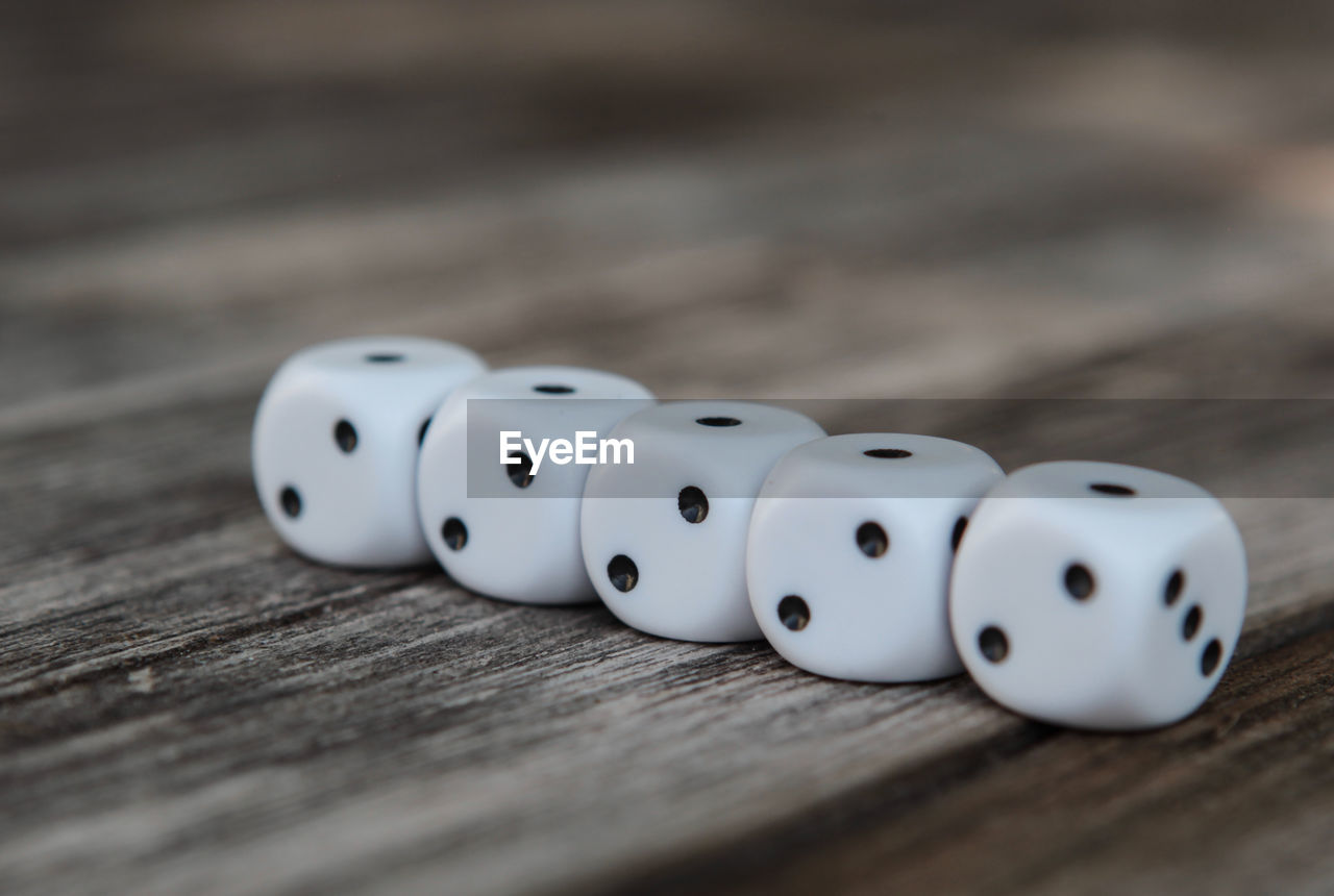 dice, table, relaxation, wood - material, leisure activity, luck, selective focus, leisure games, gambling, arts culture and entertainment, still life, opportunity, no people, spotted, close-up, high angle view, white color, indoors, surface level, cube shape, game of chance