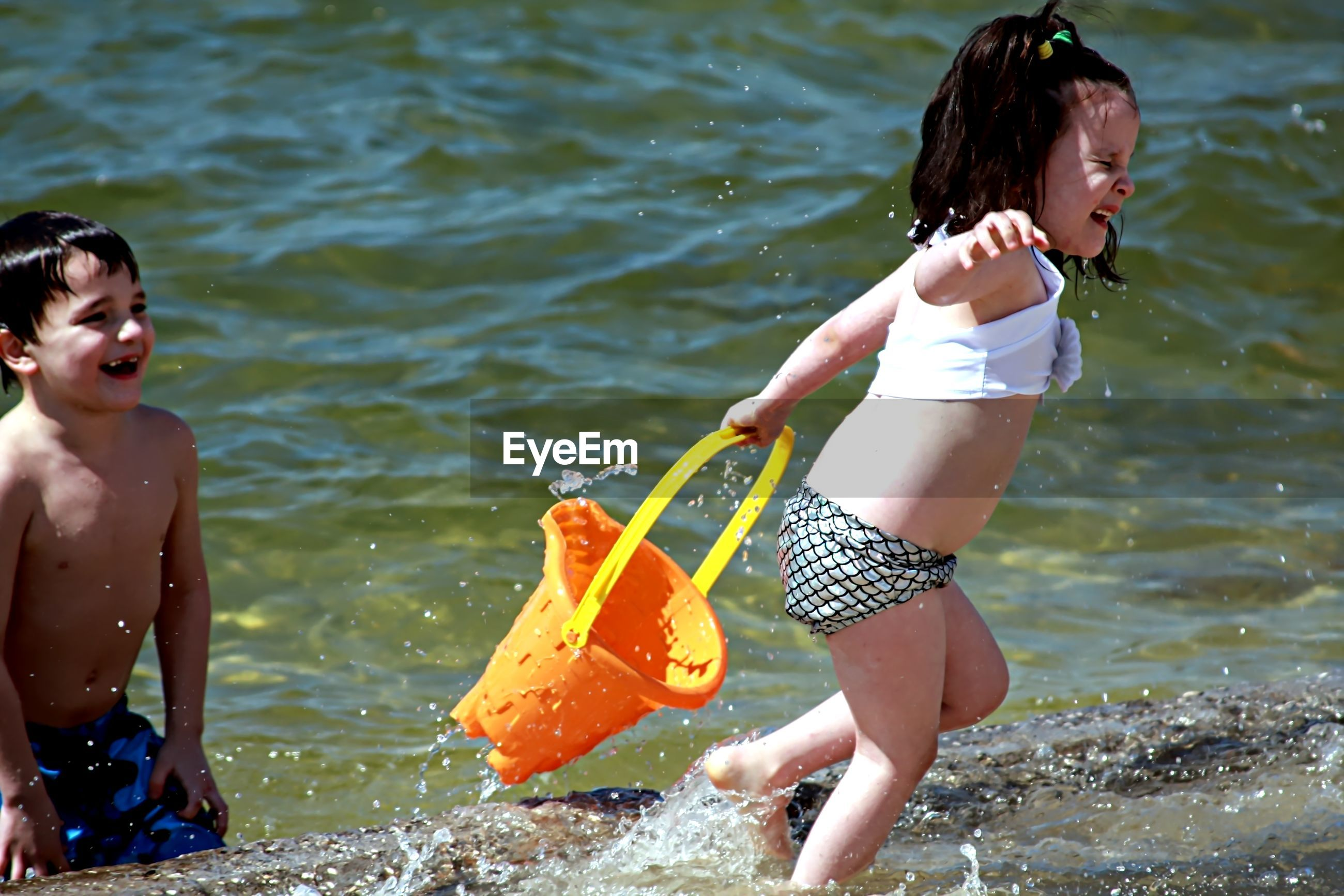 Boy and girl playing in the ocean with an orange bucket