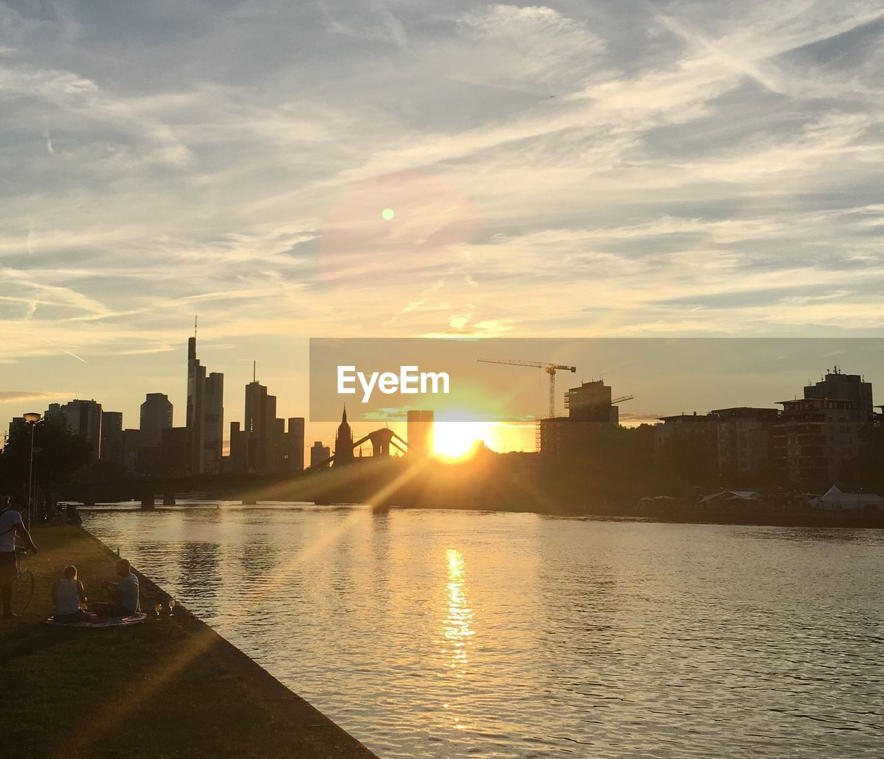 architecture, sunset, building exterior, built structure, city, skyscraper, cityscape, sky, sun, urban skyline, sunlight, cloud - sky, water, outdoors, waterfront, river, travel destinations, modern, no people, nature, day