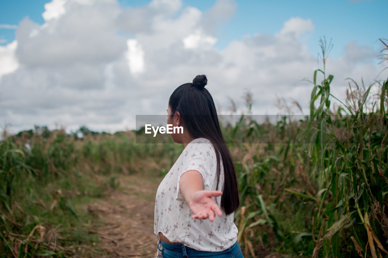 Woman standing on field against cloudy sky