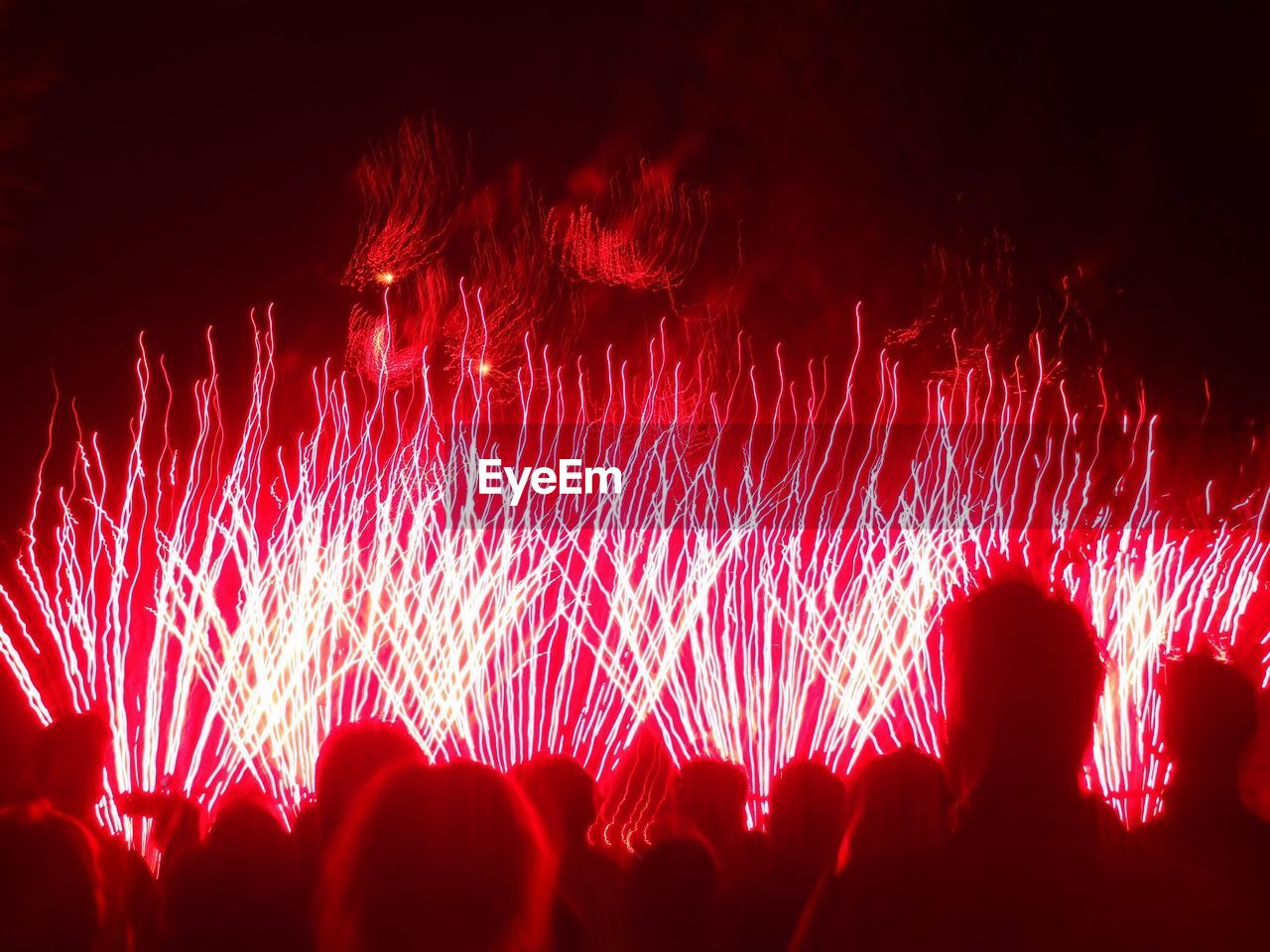 Rear view of people looking towards fireworks at night