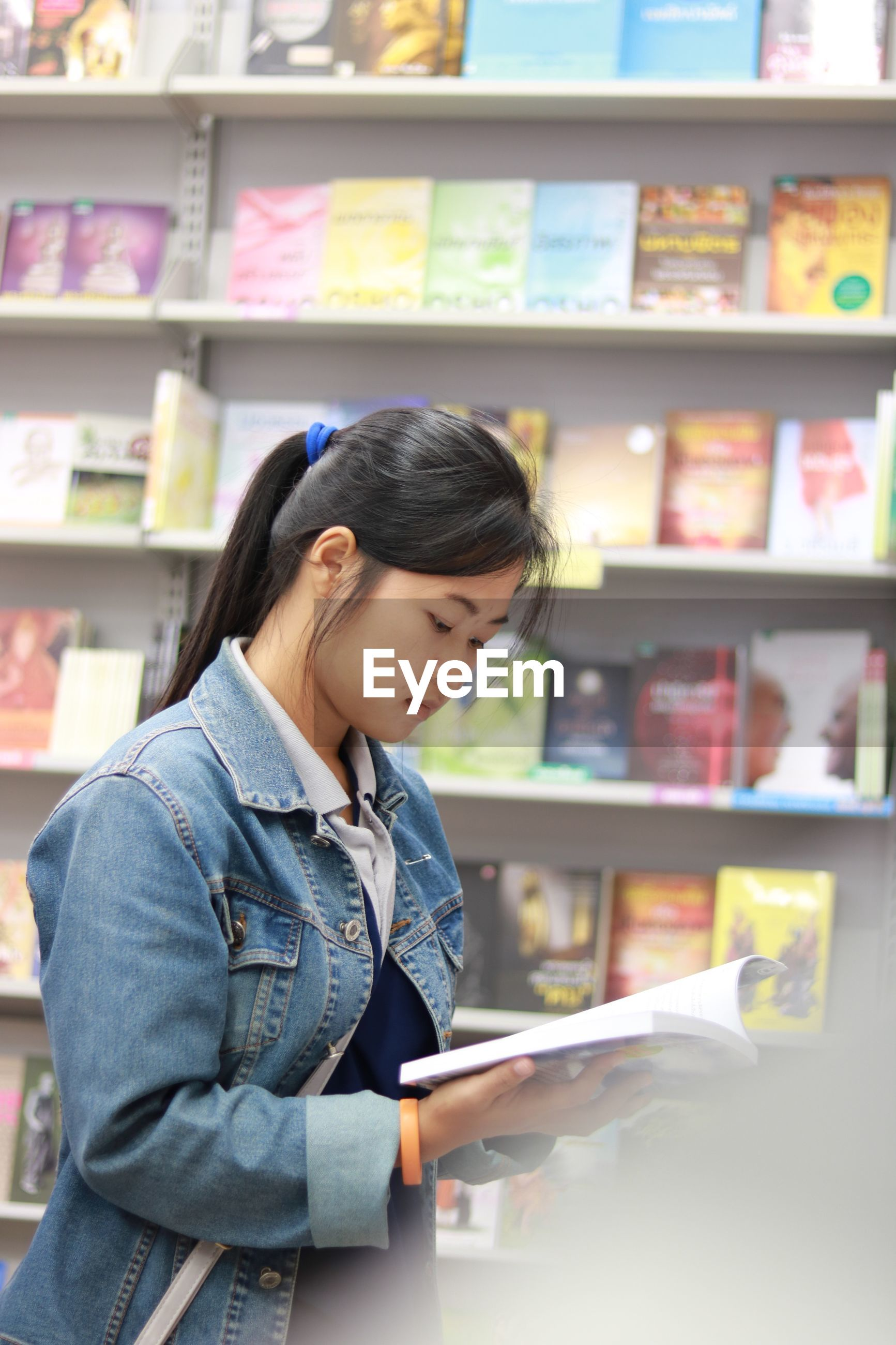 Side view of woman reading book while standing in store
