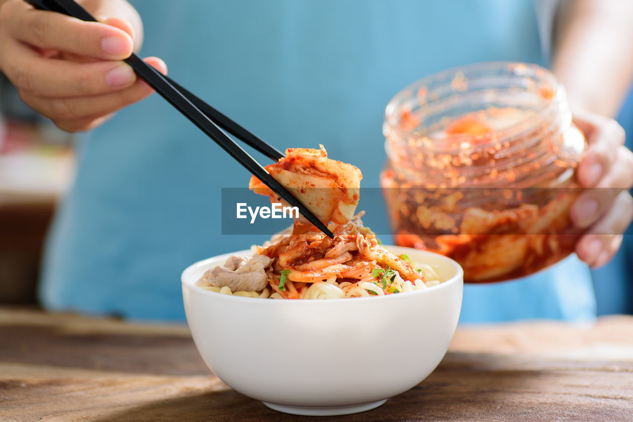 Midsection Of Woman Using Chopsticks While Picking Food From Bowl On Table