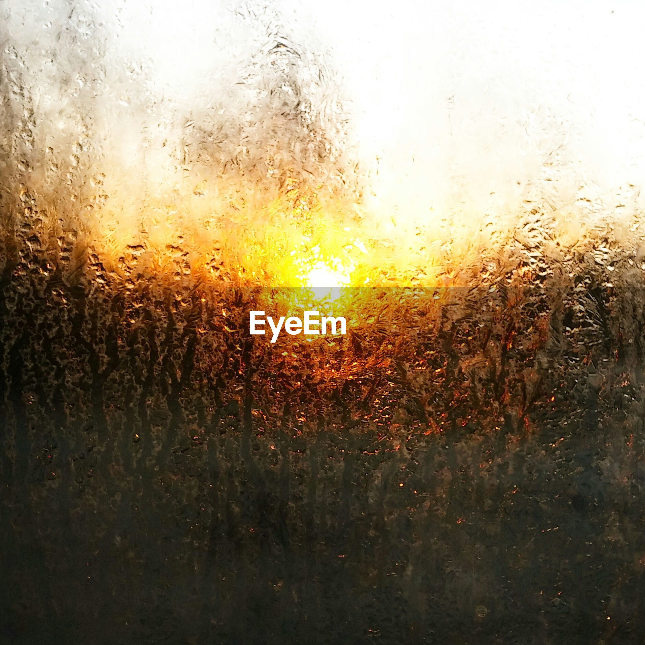 Close-up of wet glass window during sunset