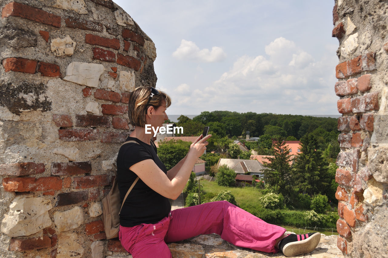 one person, real people, lifestyles, leisure activity, casual clothing, architecture, wall, young adult, wall - building feature, side view, built structure, brick, sitting, brick wall, young women, day, relaxation, building exterior, outdoors, hairstyle