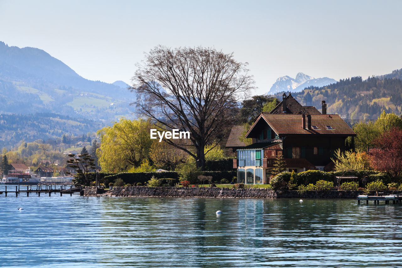 water, mountain, built structure, tree, architecture, building exterior, lake, tranquility, nature, outdoors, beauty in nature, day, scenics, sky, waterfront, no people, mountain range, clear sky