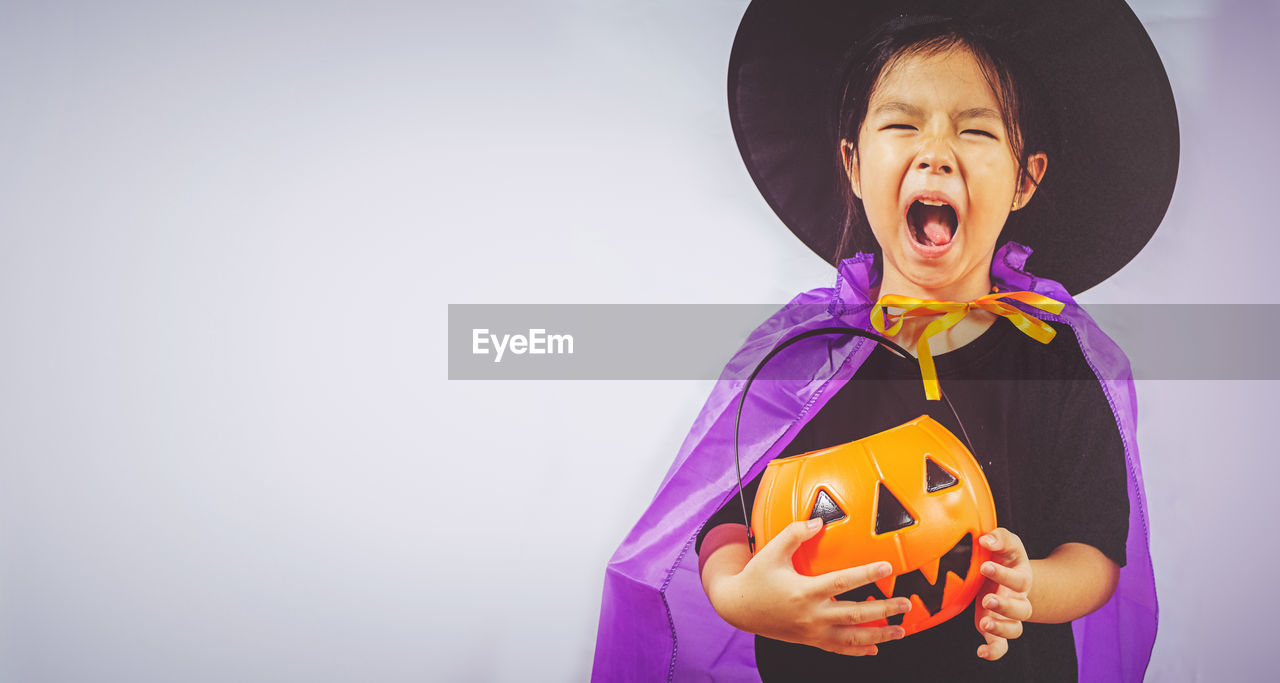 child, childhood, front view, one person, celebration, indoors, holding, real people, waist up, standing, copy space, halloween, lifestyles, clothing, smiling, studio shot, happiness, females, innocence, mouth open, jack o' lantern