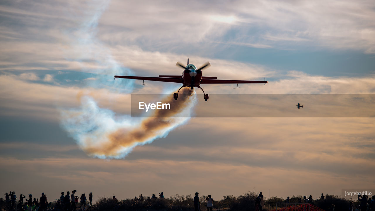 sky, cloud - sky, air vehicle, flying, mode of transportation, airplane, transportation, mid-air, airshow, on the move, low angle view, nature, motion, travel, smoke - physical structure, plane, outdoors, speed, no people, sunset, vapor trail, aerospace industry