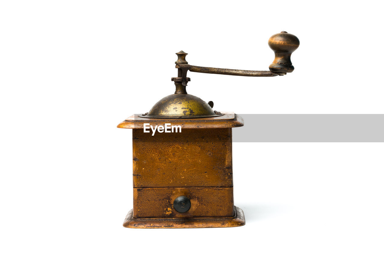 Close-up of antique coffee grinder against white background