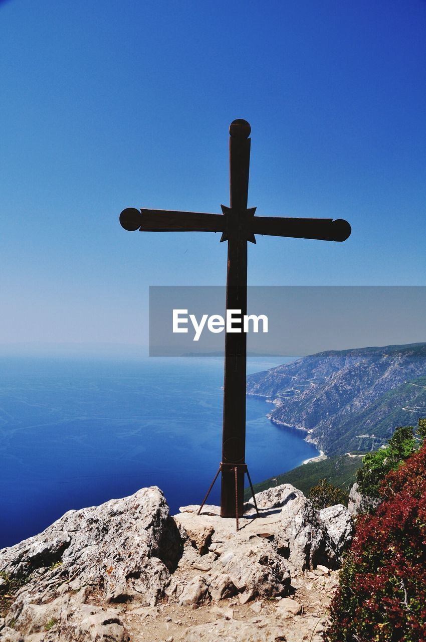 High Angle View Of Cross On Cliff By Sea Against Clear Blue Sky