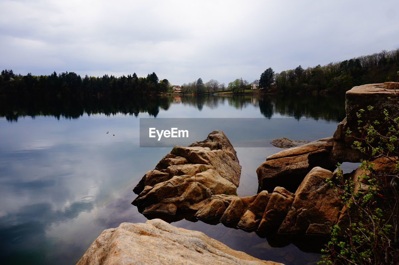 SCENIC VIEW OF LAKE BY ROCKS AGAINST SKY