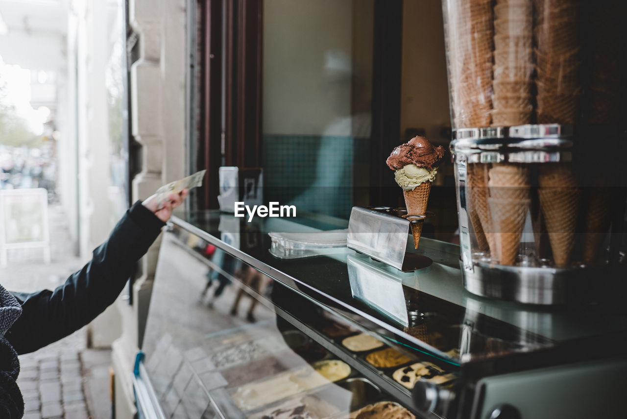 Cropped hand of person paying at ice cream store