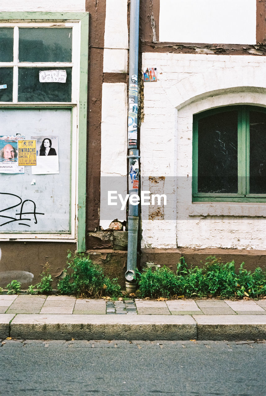 architecture, built structure, building exterior, building, day, no people, communication, window, outdoors, wall - building feature, old, plant, door, wall, footpath, entrance, city, nature, sign, house