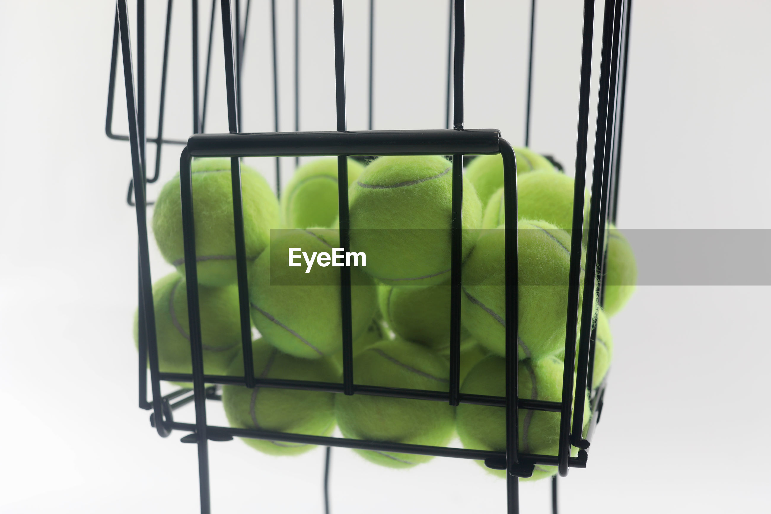 Close-up of tennis balls in basket against white background