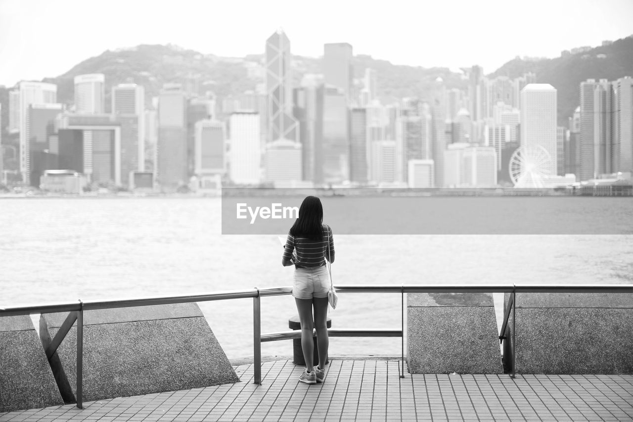 Rear View Of Young Woman Standing On Promenade By Sea Against City