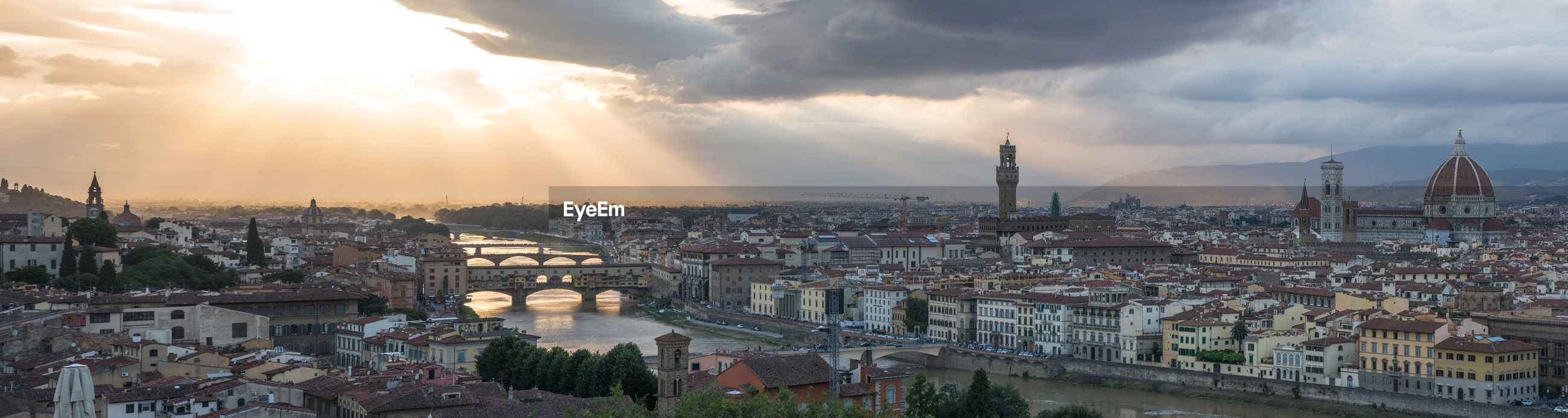 Panoramic shot of arno river amidst cityscape against sky during sunset