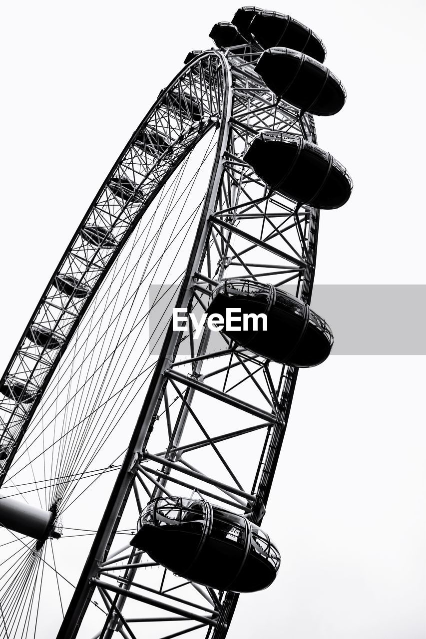 sky, low angle view, amusement park, ferris wheel, amusement park ride, nature, clear sky, arts culture and entertainment, day, built structure, metal, architecture, fairground, leisure activity, outdoors, tall - high, no people, spinning, enjoyment, geometric shape