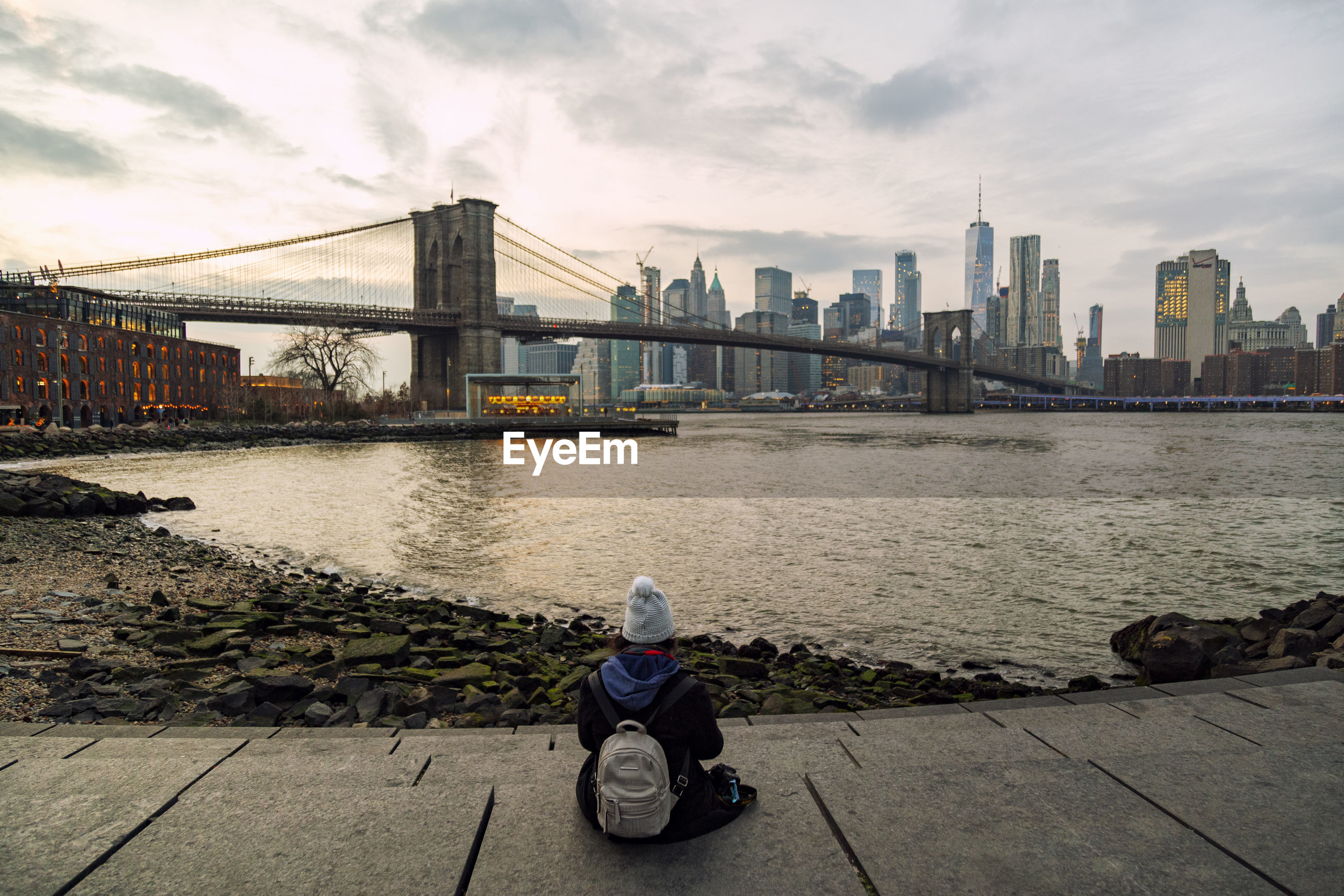 Rear view of woman looking at bridge over river in city