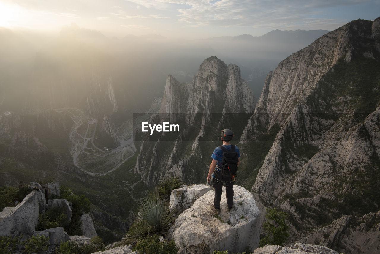 FULL LENGTH OF MAN ON ROCKS AT MOUNTAIN