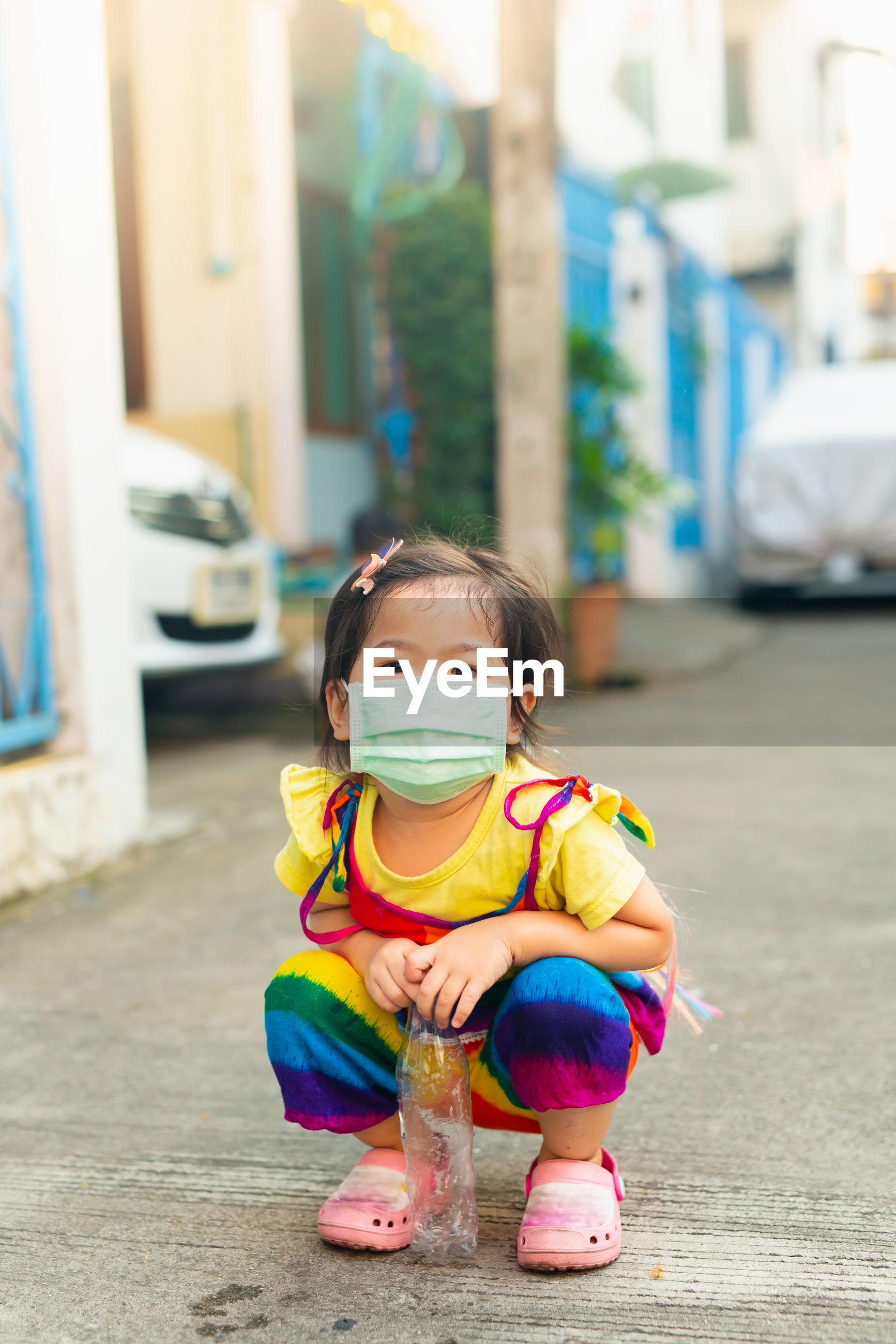 Portrait of girl wearing mask crouching on road