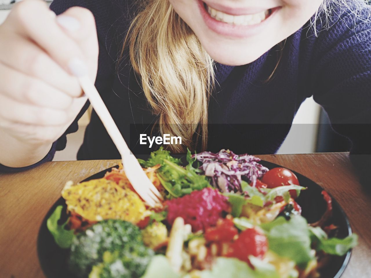 Midsection of happy woman eating salad at table