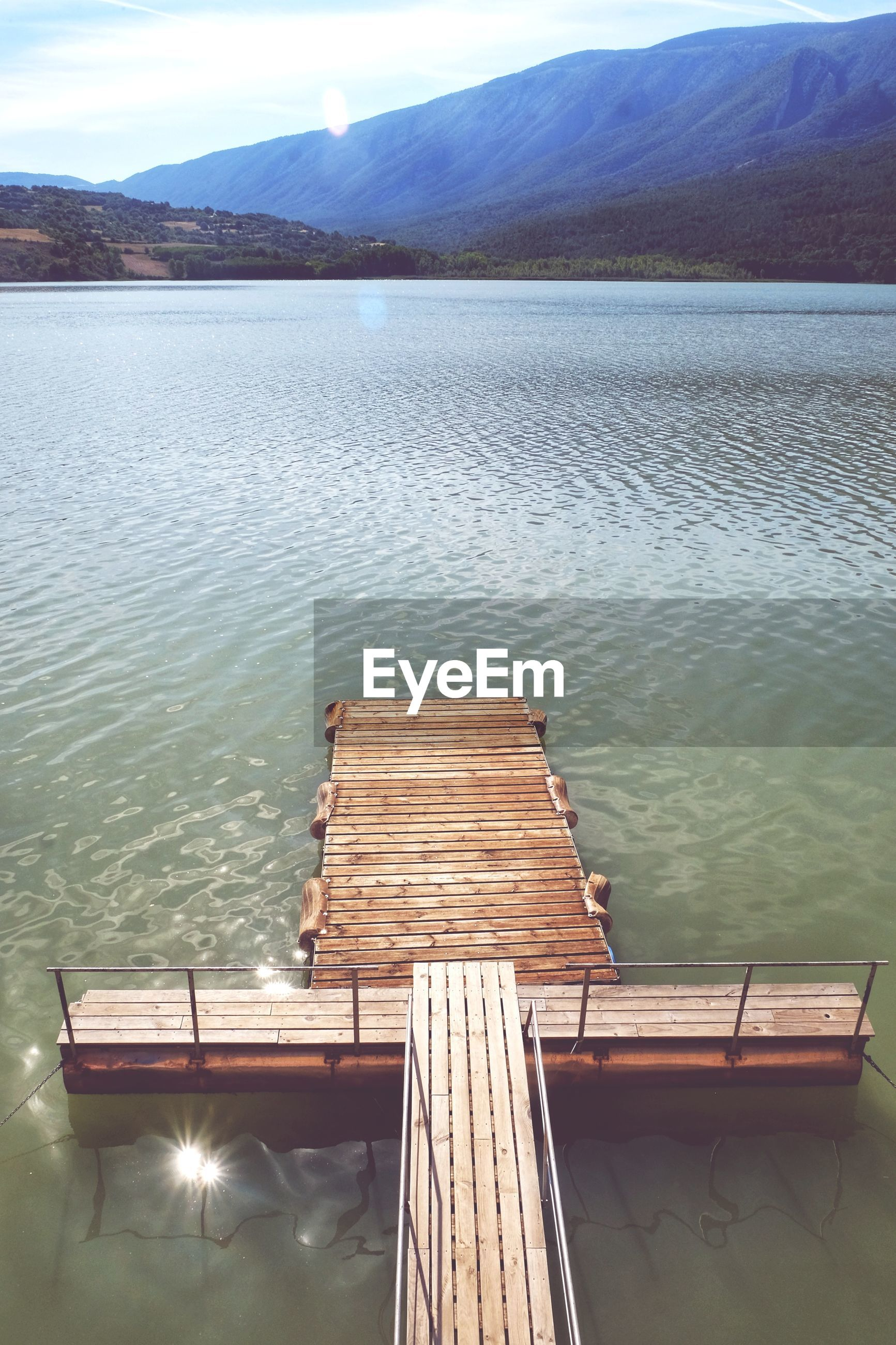 HIGH ANGLE VIEW OF WOODEN PIER OVER LAKE AGAINST SKY