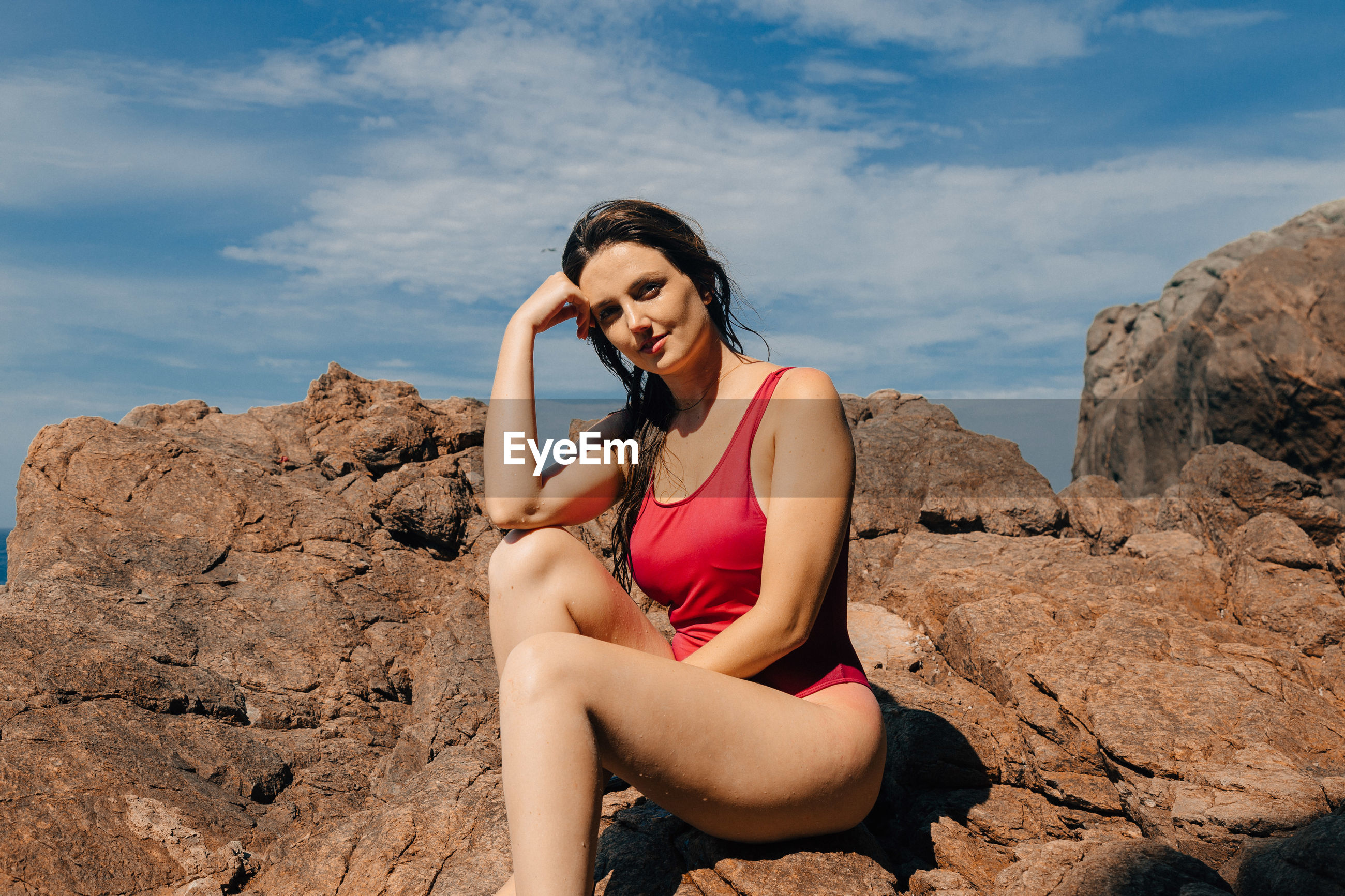 Portrait of sensuous young woman sitting on rock against sky
