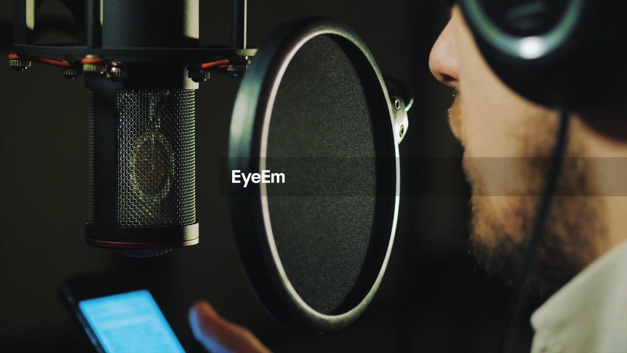 Close-Up Of Man Singing At Recording Studio