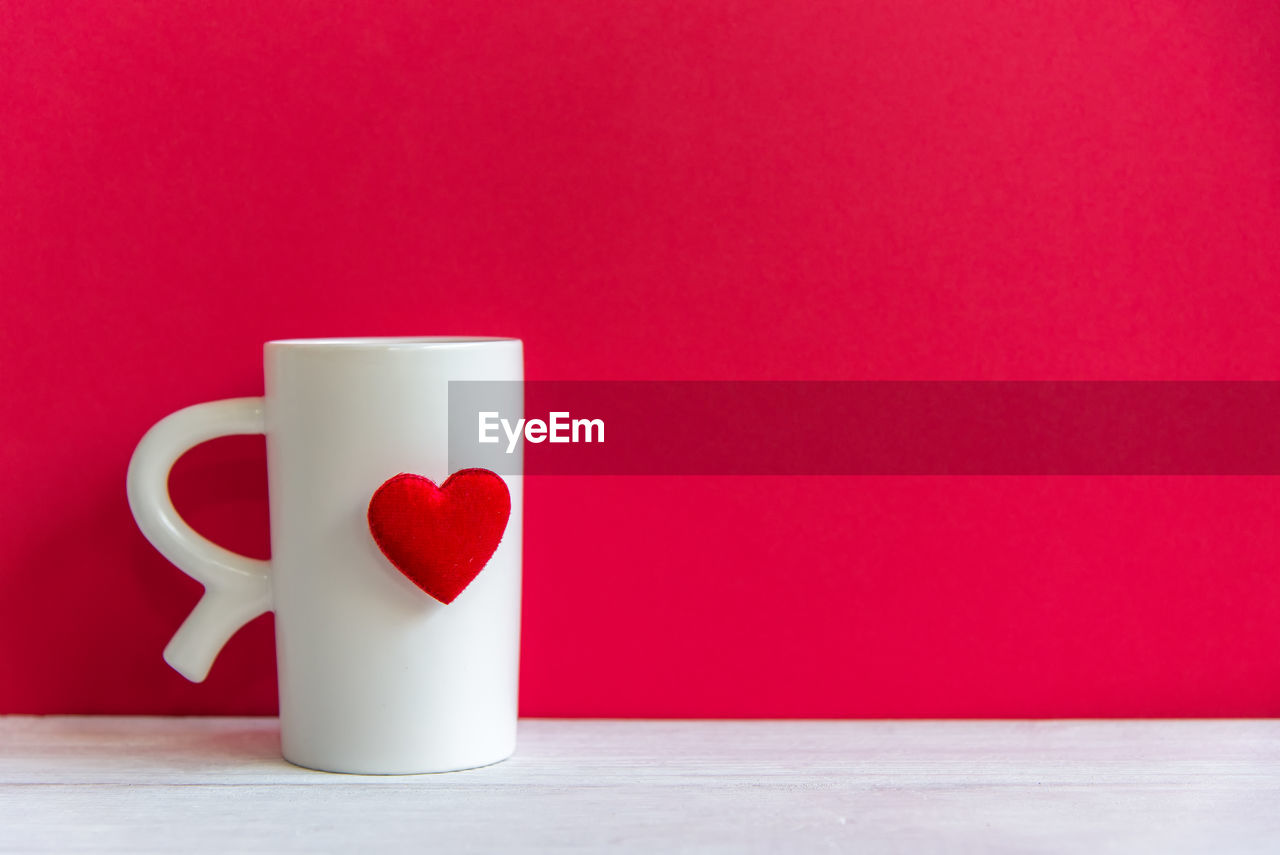 CLOSE-UP OF COFFEE CUP ON TABLE AGAINST RED BACKGROUND