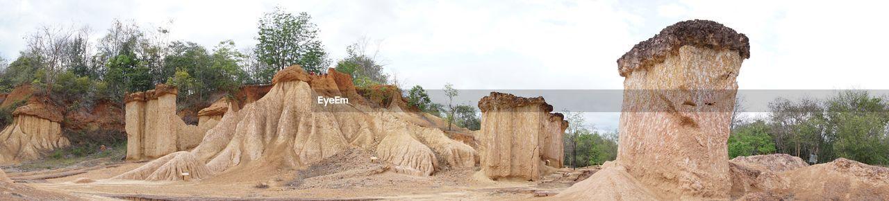PANORAMIC SHOT OF ROCKS ON LANDSCAPE AGAINST SKY