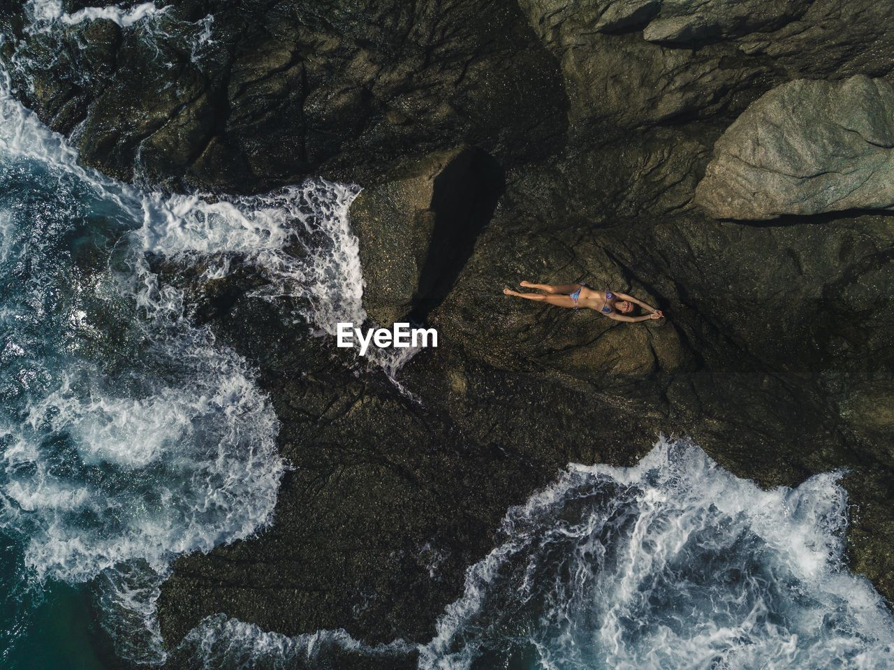 Full Length Of Woman Lying On Rock