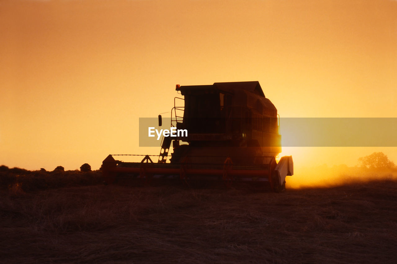 sunset, sky, transportation, land vehicle, mode of transportation, nature, orange color, land, field, landscape, sun, machinery, environment, copy space, outdoors, sunlight, agricultural machinery, rural scene, clear sky, agriculture