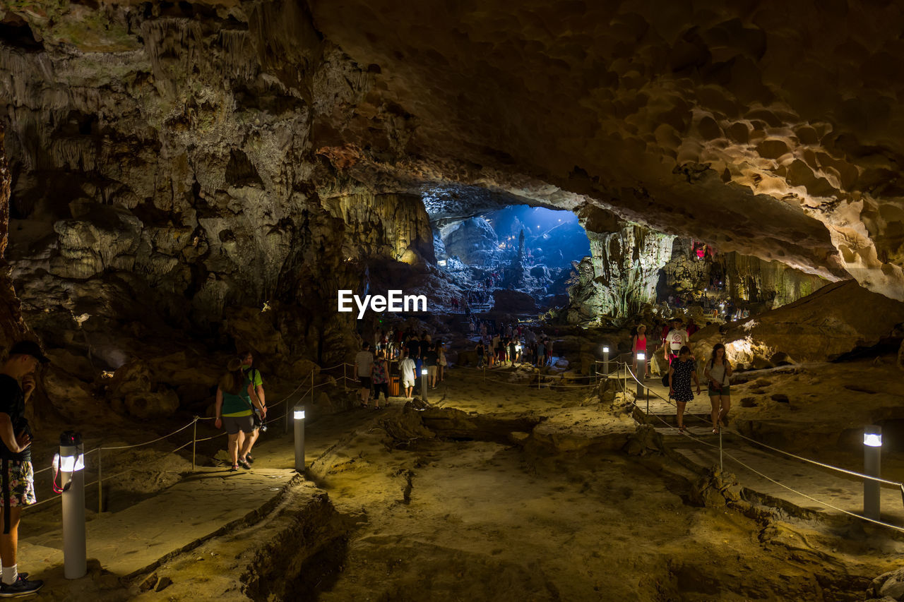 illuminated, group of people, cave, night, lighting equipment, real people, architecture, indoors, incidental people, nature, men, lifestyles, group, rock, rock - object, built structure, people, medium group of people, electric light, light