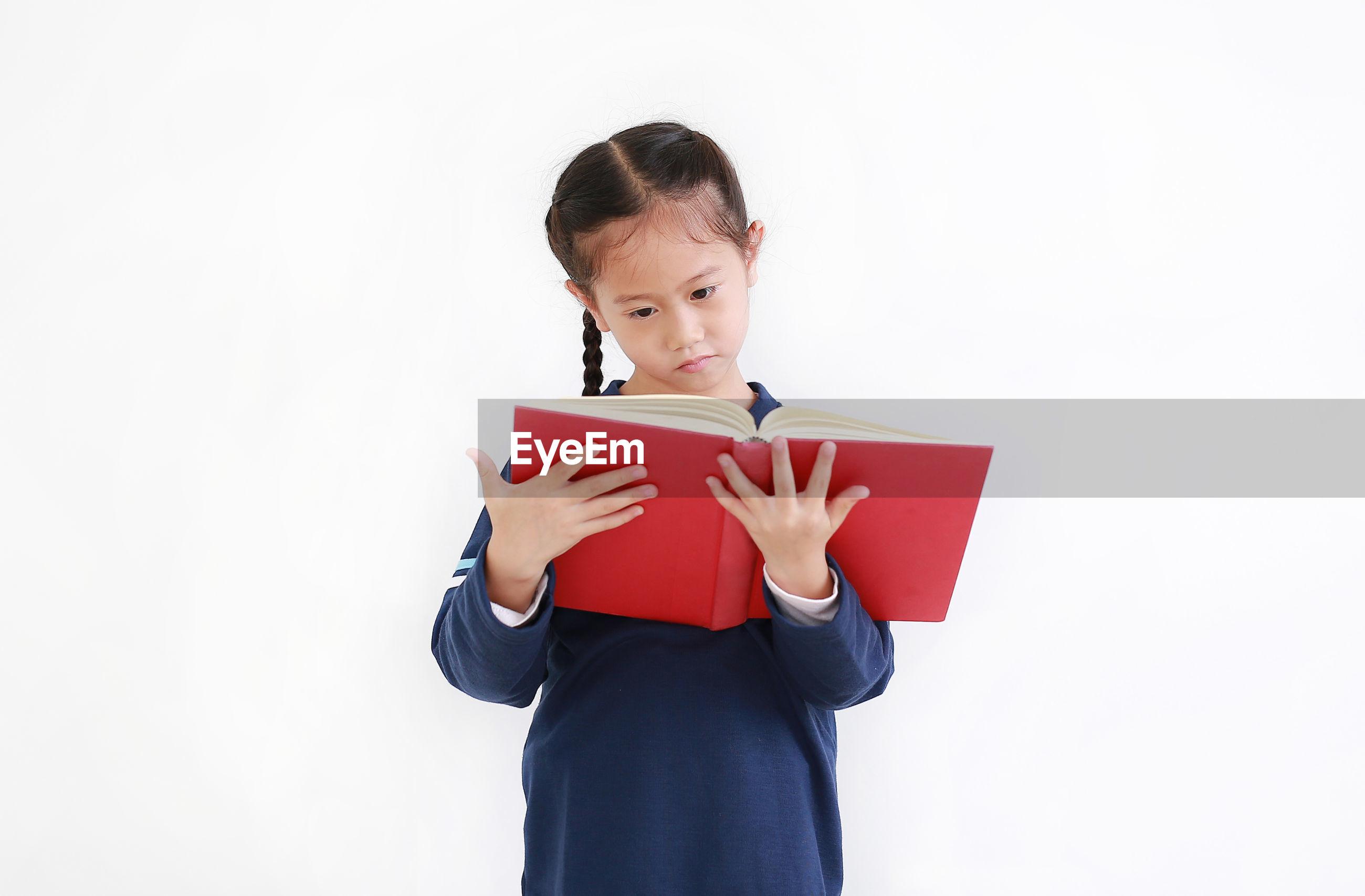 FULL LENGTH OF A GIRL HOLDING BOOK