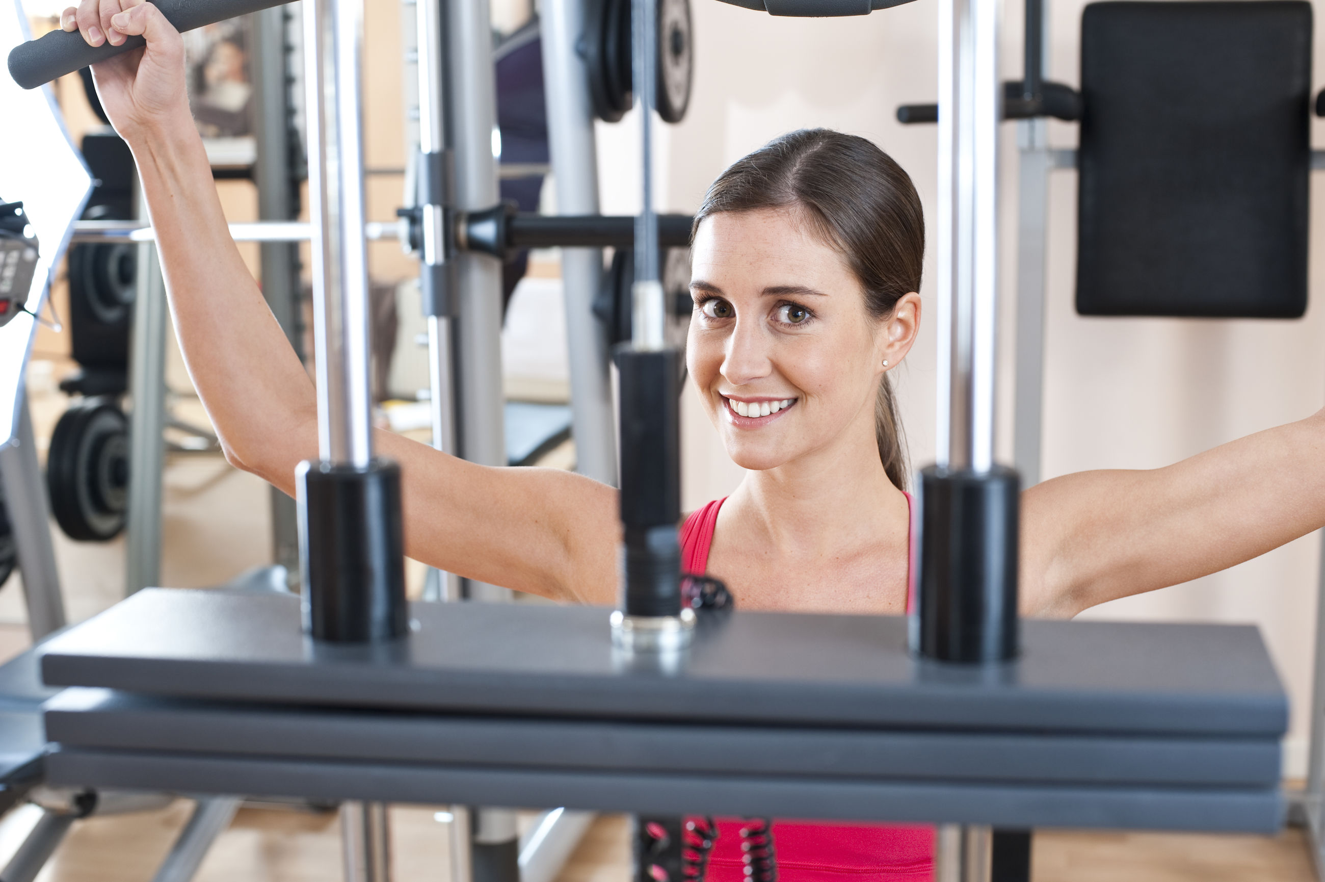 Close-up of smiling woman exercising at gym