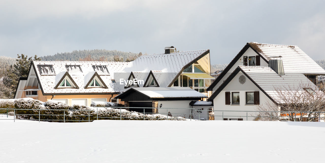 HOUSES BY TREES ON SNOW COVERED HOUSE AGAINST SKY