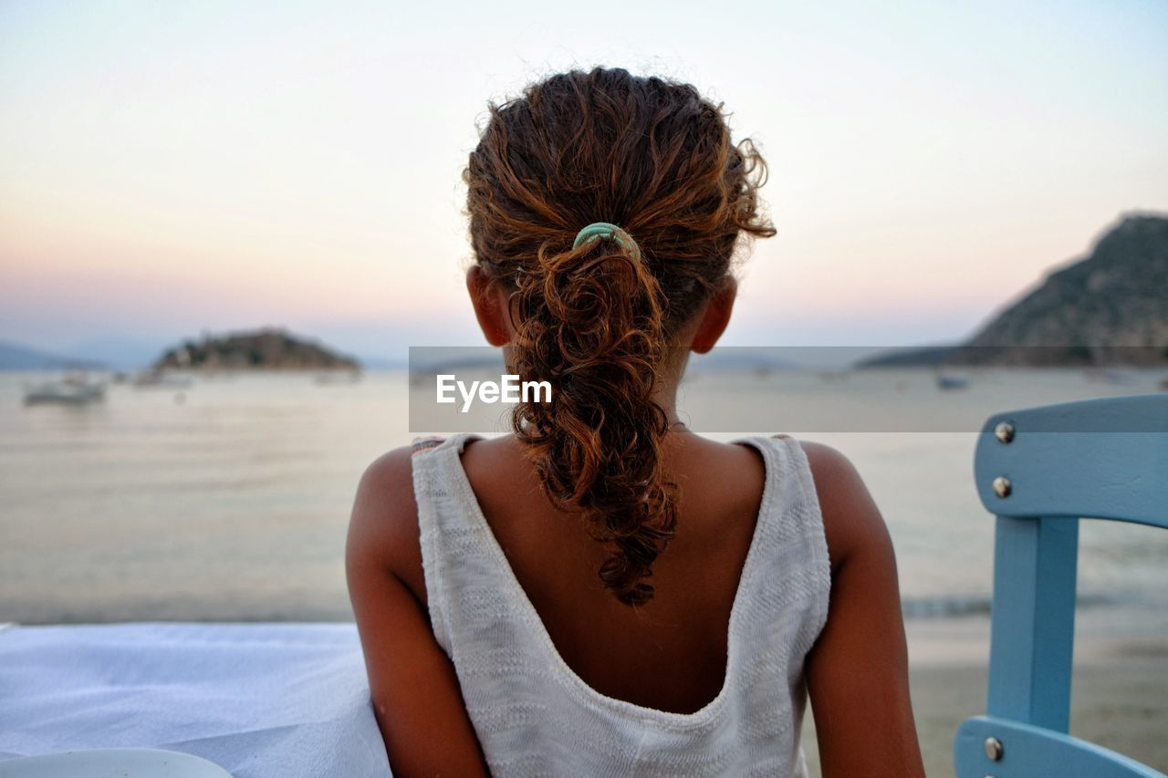 Rear view of girl sitting at beach