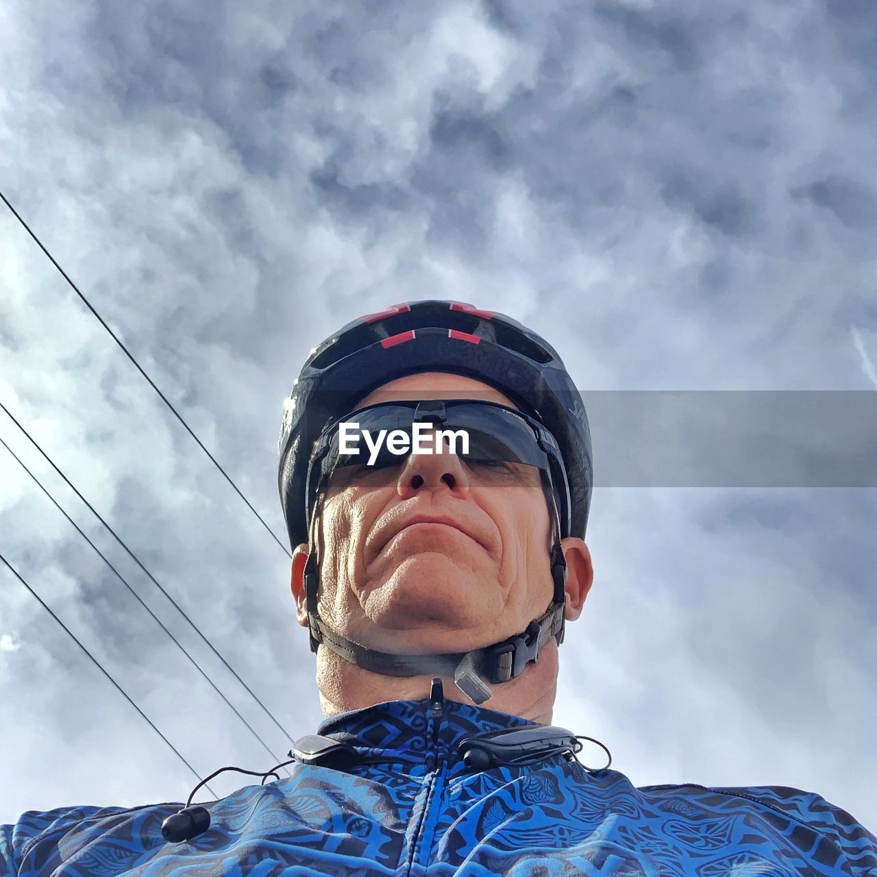 Low angle view of man wearing bicycle helmet against sky