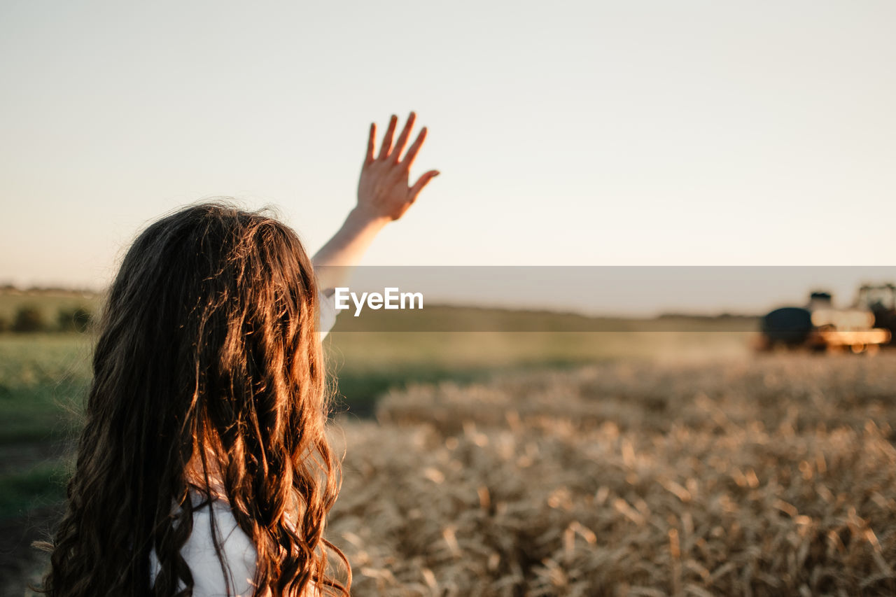 Side view of woman gesturing while standing in farm