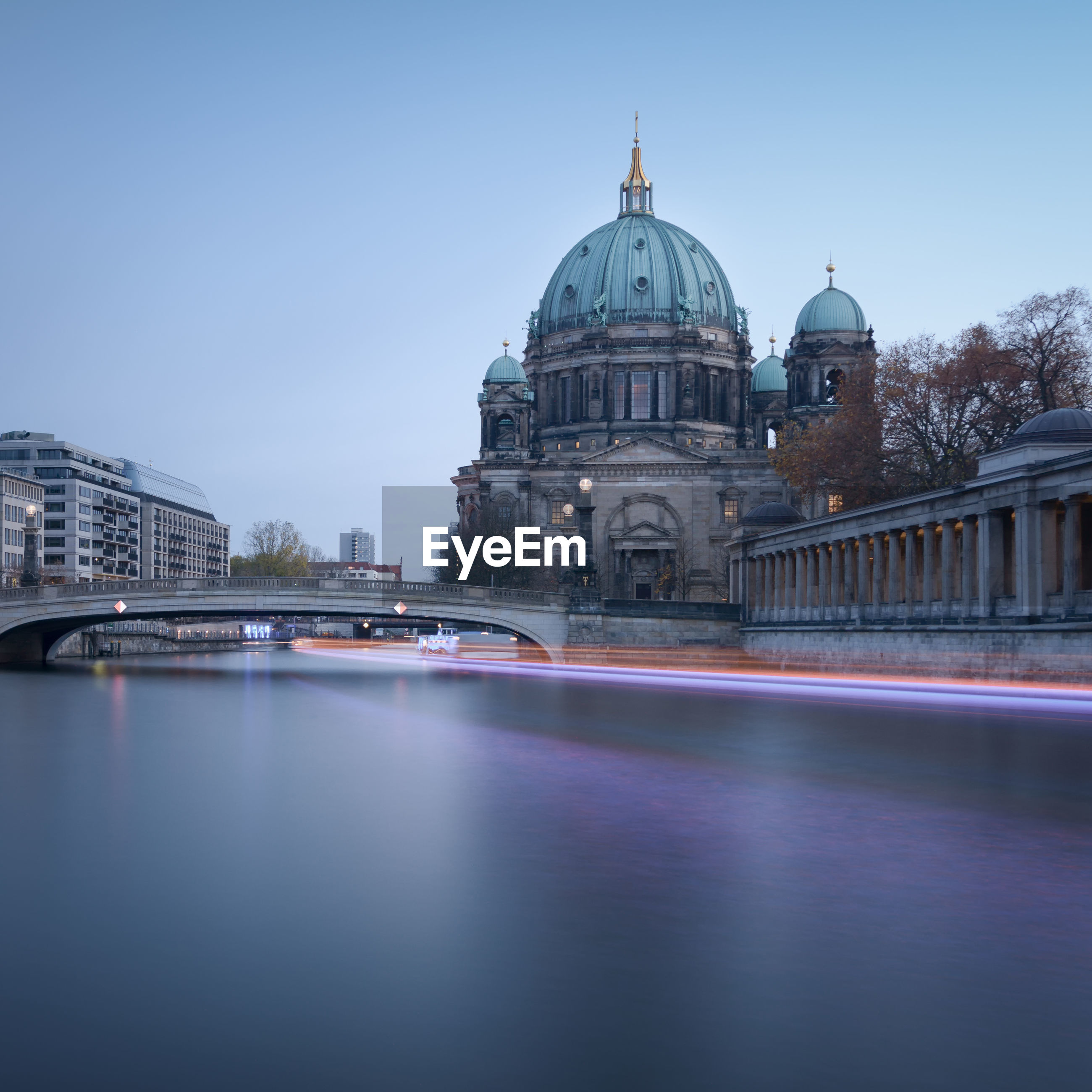 Light trail over river by berlin cathedral against clear sky at dusk