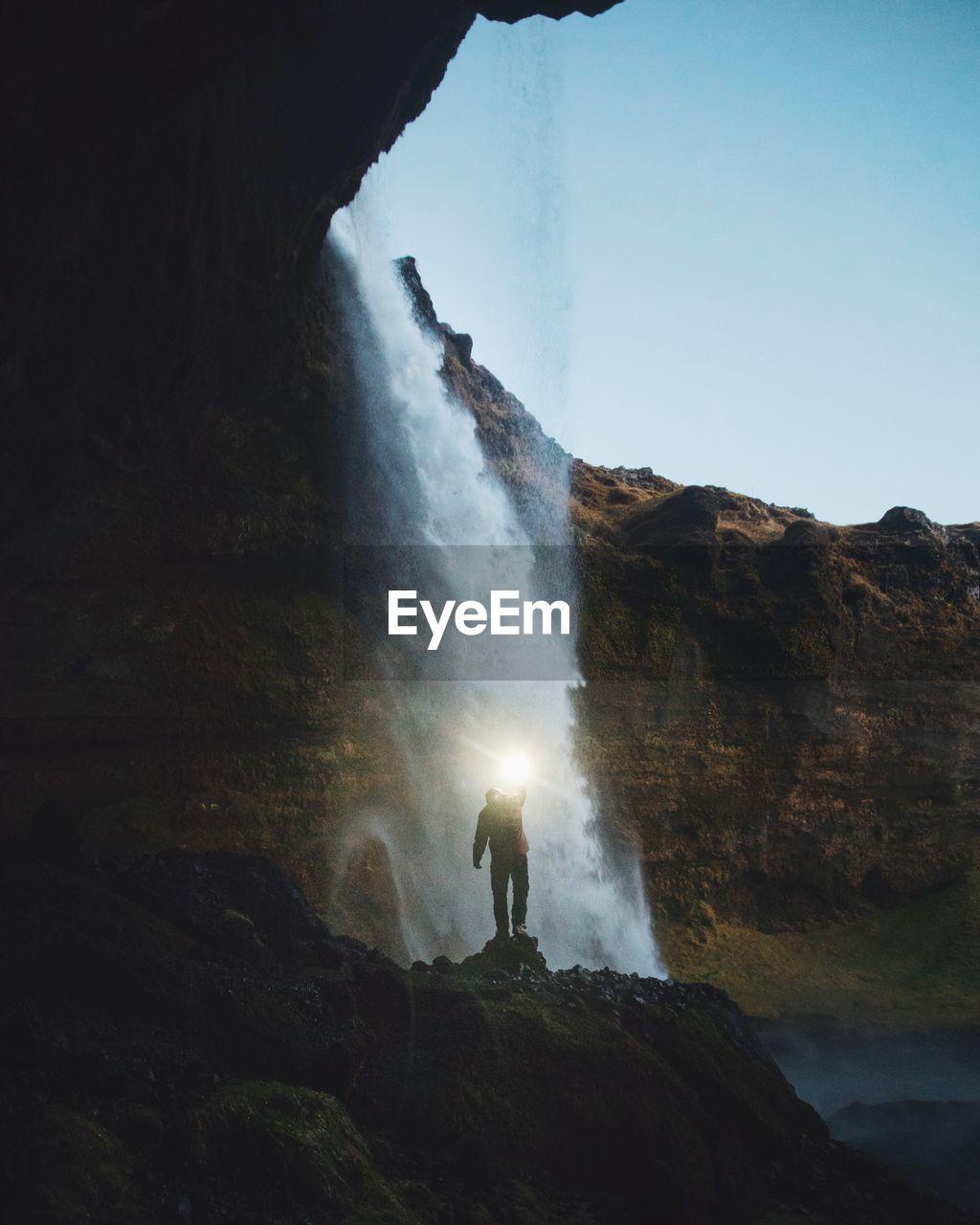 Man Standing Against Waterfall