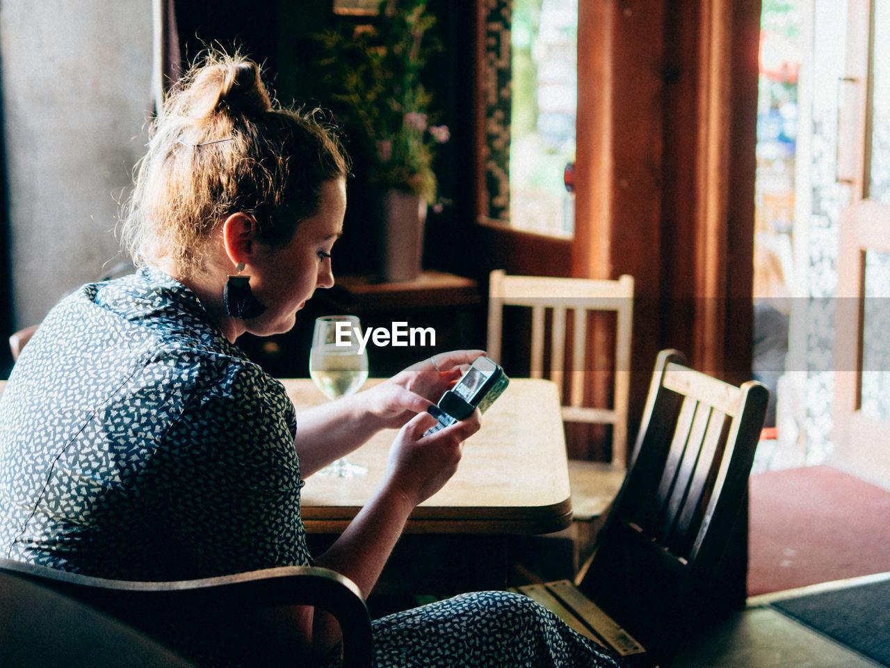 Woman Using Mobile Phone In Bar