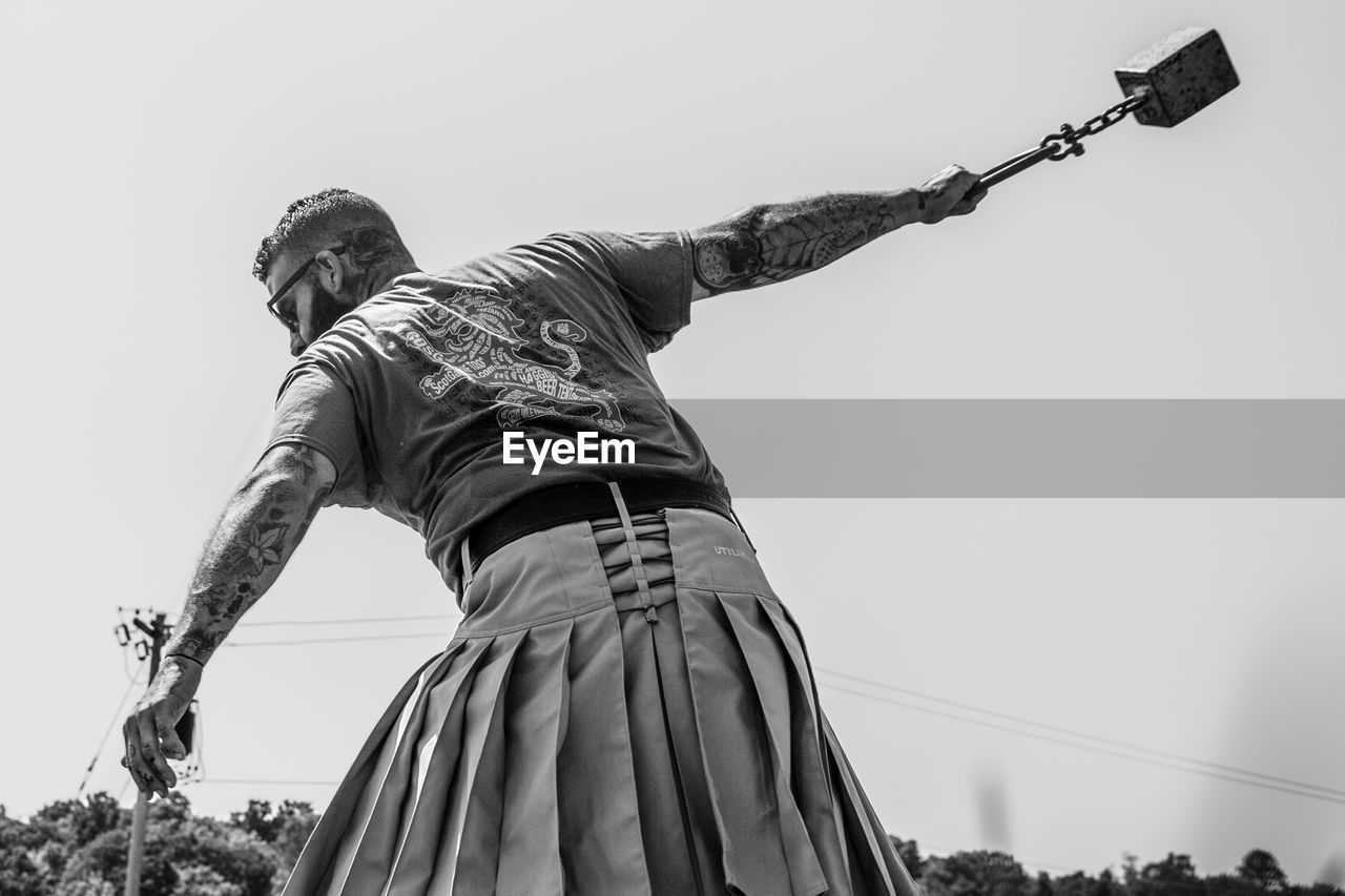 statue, low angle view, clear sky, outdoors, sculpture, day, sky, real people, one person, people