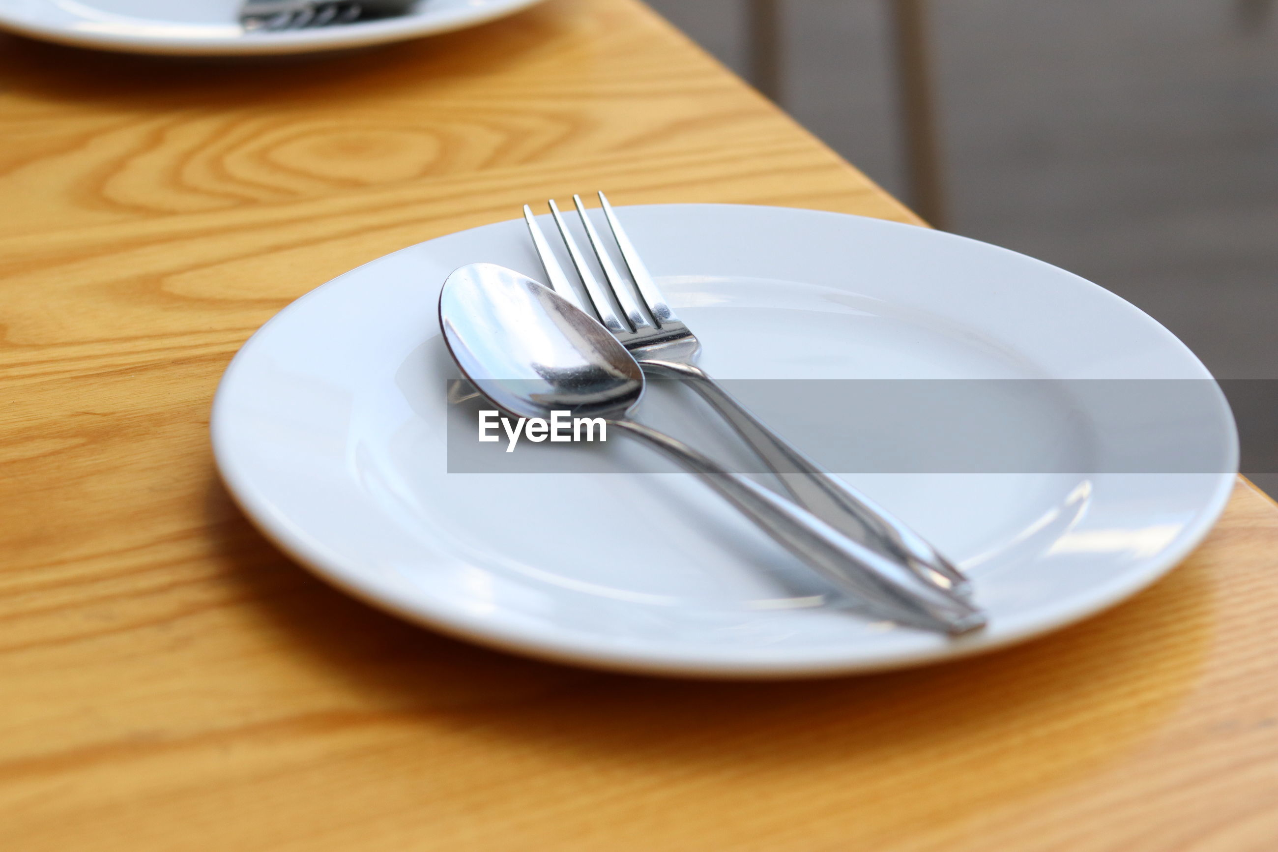 High angle view of fork and spoon in plate on wooden table