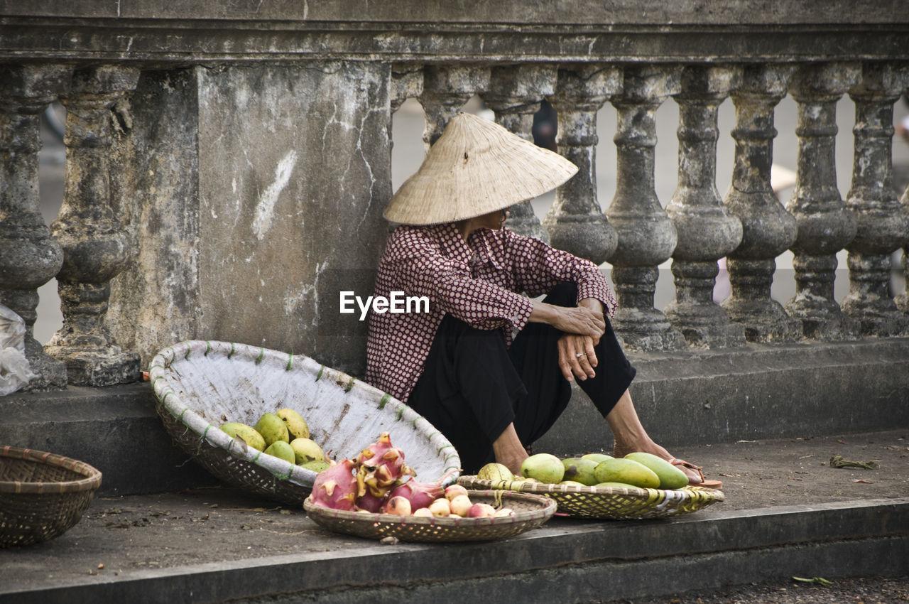Vendor Selling Fruits On Sidewalk Against Railing