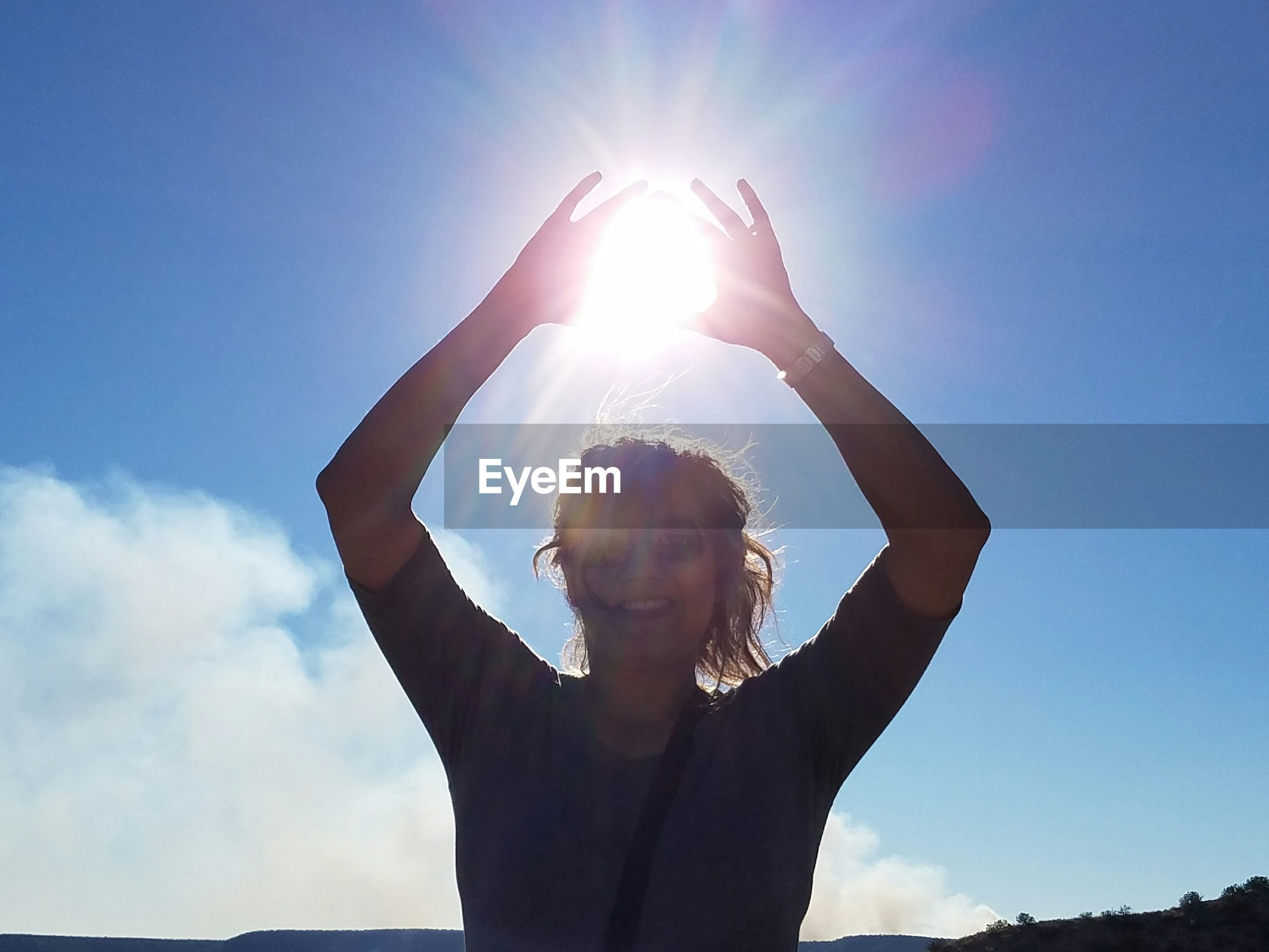 Happy woman with arms raised standing against blue sky on sunny day