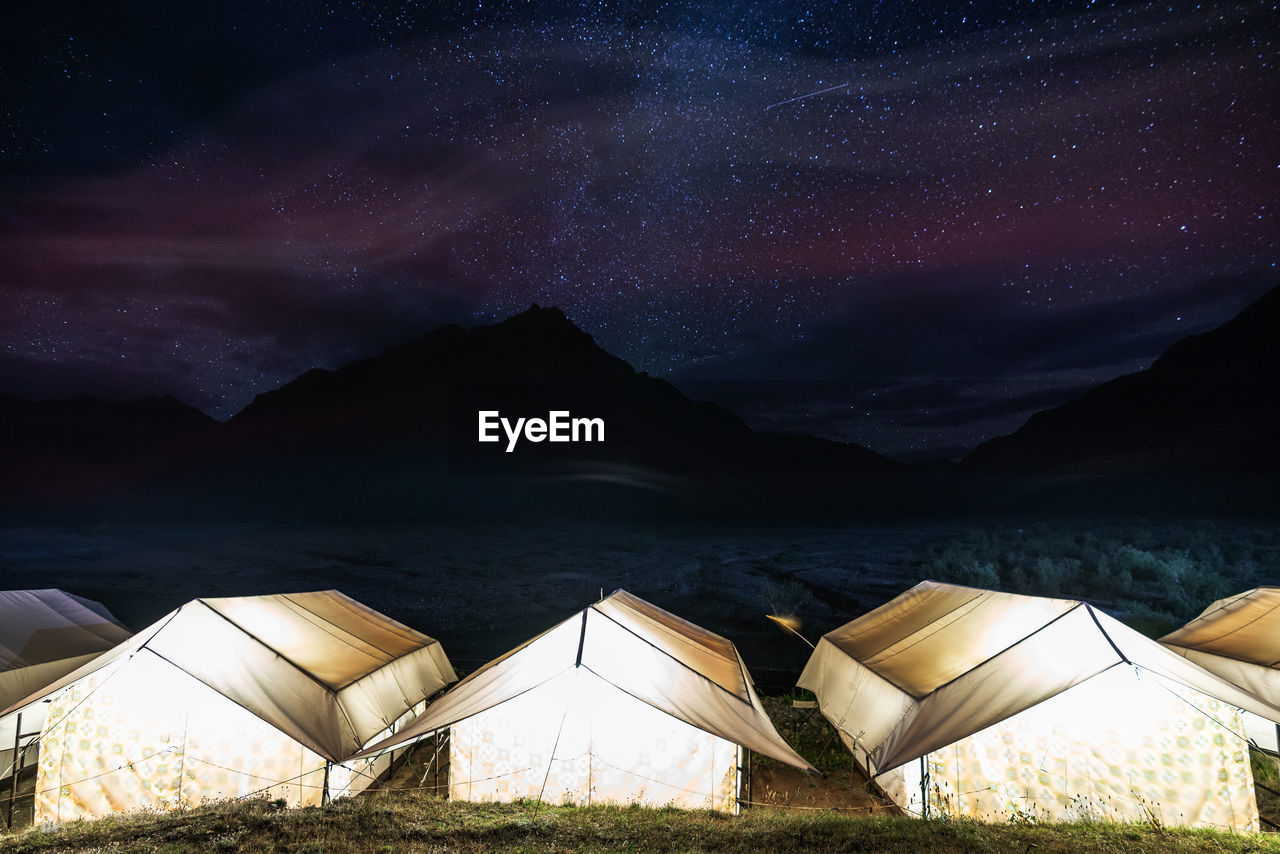 Illuminated Tents Against Star Field At Night