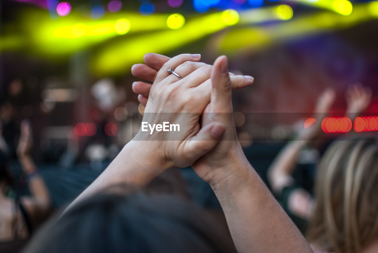 Cropped image of woman with hands clasped at concert