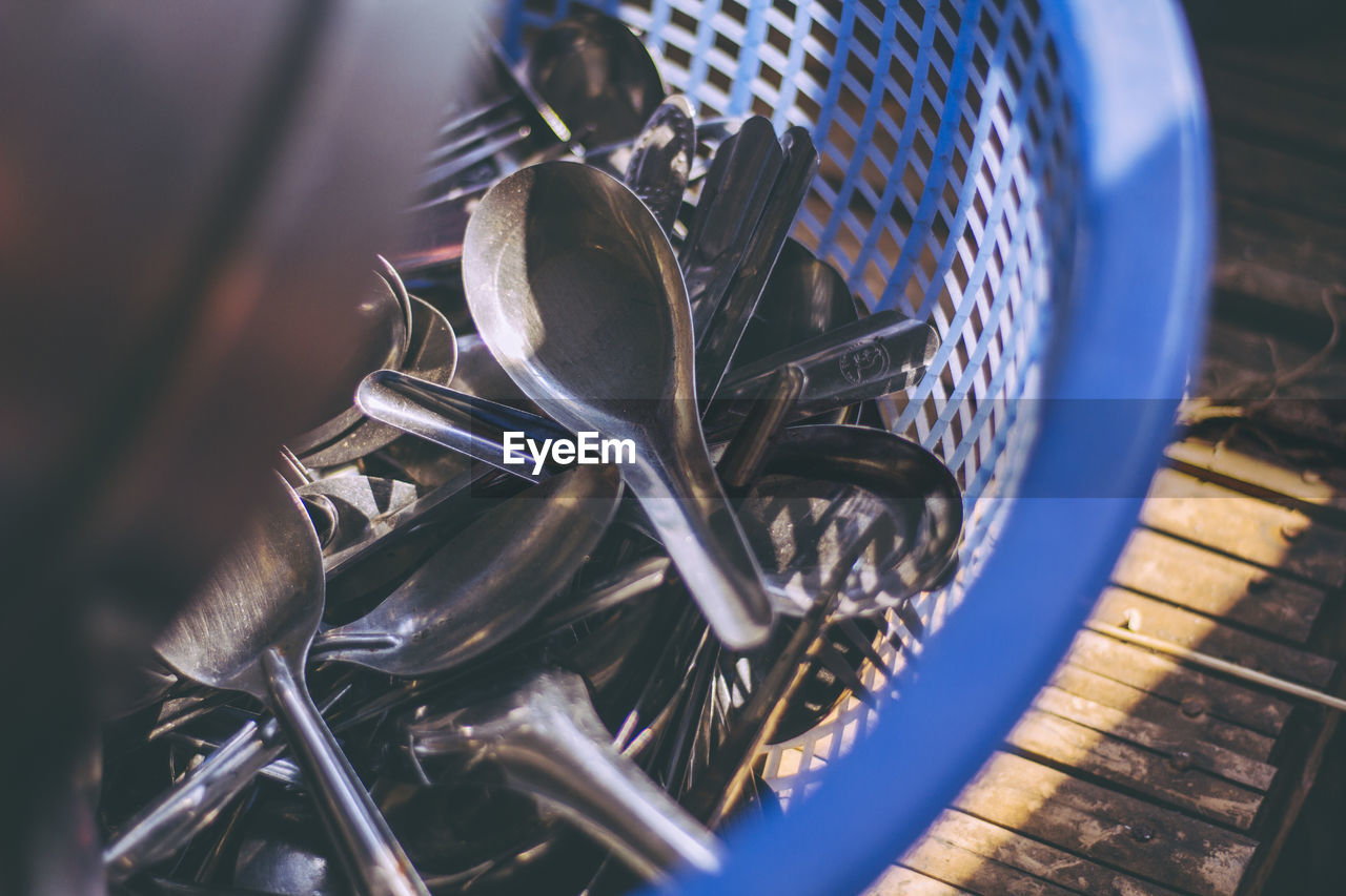 metal, selective focus, close-up, no people, bicycle, container, basket, high angle view, day, still life, land vehicle, large group of objects, nature, outdoors, silver colored, blue, pattern, sunlight, focus on foreground, steel